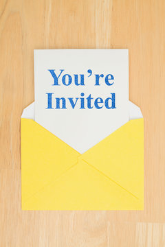 You're Invited message on white card with a yellow envelope