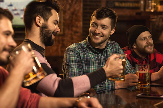 Happy male friends enjoying beer together at the bar