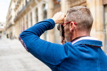 Rear view of a photographer man taking photo in the street