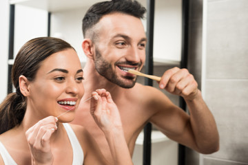 bearded boyfriend brushing teeth near girlfriend using dental floss in bathroom
