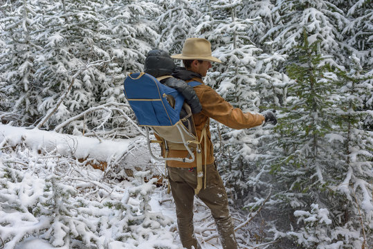 Person hiking through snowy forest