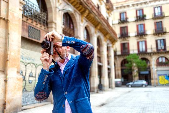 Stylish photographer man taking photo in the street
