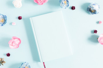 Flowers composition creative. Notebook, pink and light blue flowers on pastel blue background. Flat lay, top view, copy space