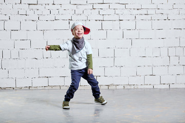 cheerful child boy dancing to music. Cool boy hip hop. Cute fashionable naughty kid. Little rapper man wears a cap, sneakers, pants, t-shirt, street style clothes. studio, brick wall background.