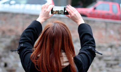 view from the back at the woman who takes pictures on the smartphone