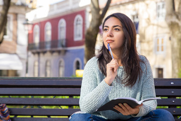 Pensive woman holding pen and copy-book on bench outdoors