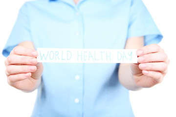 Paper with text World Health Day in female hands