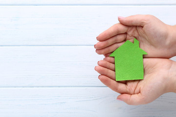 Female hands holding green paper house on wooden background