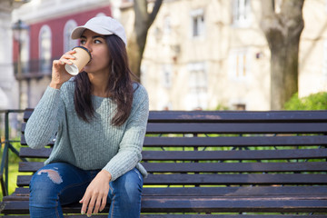 Pretty young woman drinking coffee and sitting on bench outdoors
