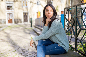 Serious pretty young woman sitting on stone bench outdoors