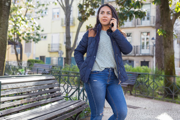 Serious woman calling on mobile phone outdoors