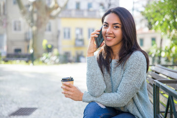 Smiling lady calling on phone and holding plastic cup on bench