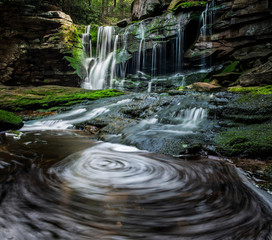 Scenic view of stream flowing against waterfall in forest