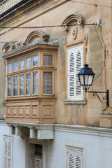 Traditional, wooden balcony and stone facade, typical for architecture of Gozo, Malta