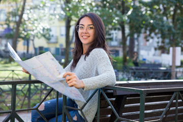 Smiling pretty young woman using paper map on bench outdoors