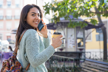 Smiling woman calling on phone and holding drink outdoors