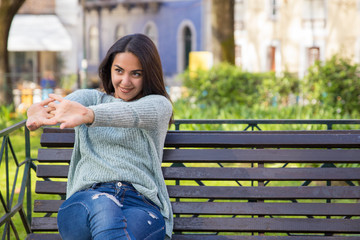 Smiling woman stretching arms and sitting on bench outdoors