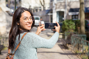Smiling woman turning around and taking selfie photo outdoors