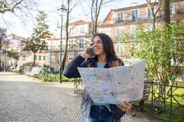 Smiling woman using paper map and walking outdoors