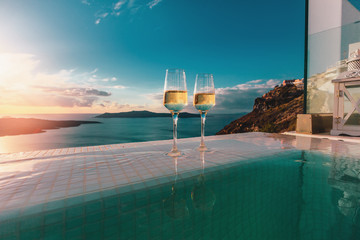 Two champagne glasses on the edge of infinity swimming pool at sunset on Santorini island