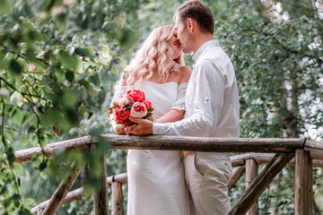 Groom bride posing on a wooden bridge