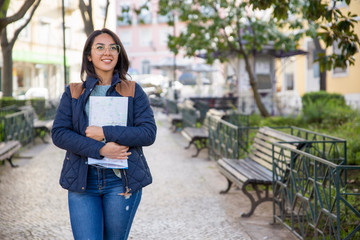 Smiling woman walking outdoors and holding folded map