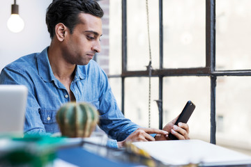 Businessman using phone while sitting at desk in office