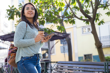 Smiling woman with smartphone and plastic cup outdoors