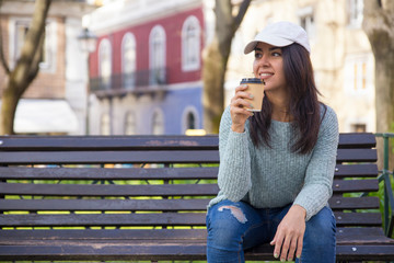 Smiling young woman drinking coffee and sitting on bench