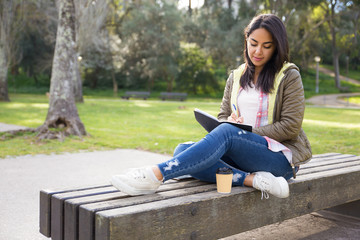 Pensive Asian girl making notes in diary while sitting in park
