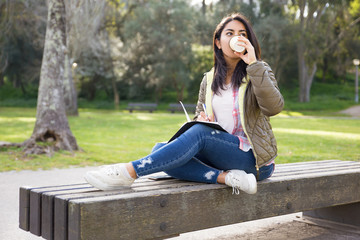 Pensive Asian student girl drinking coffee in park