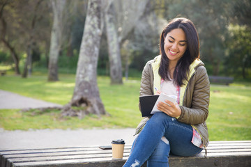 Positive young woman in jacket sitting on bench in city park