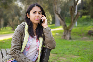Serious young woman talking on mobile phone in park
