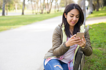 Smiling content woman reading message on smartphone