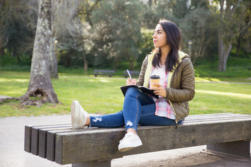 Thoughtful young woman making home task in park