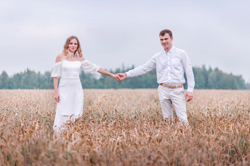 Bride and groom holding hands on the background of a wheat field