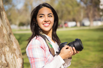 Cheerful smiling young photographer posing with camera