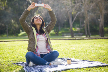 Delighted student girl taking selfie on phone outdoors