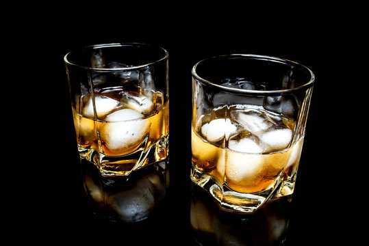 Whiskey with ice close up on a glass table isolated on a black background