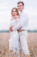 Bride and groom posing against the backdrop of a wheat field