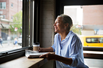 Smiling woman with newspaper and coffee looking through window at table in cafe