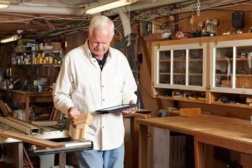 Carpenter using tablet computer in workshop