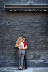 Full length of loving couple standing against wall