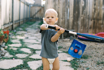 Portrait of boy holding baseball bat while standing in backyard
