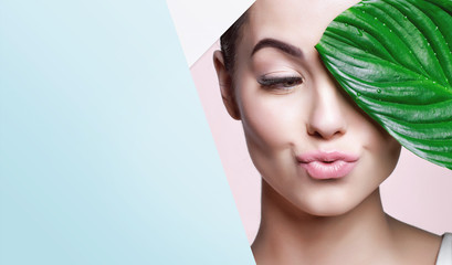 Portrait of young beautiful woman with healthy glow perfect smooth skin holds green tropical leaf, look into the hole of colored paper. Model with natural nude make up. Fashion, beauty, skincare. Wall mural