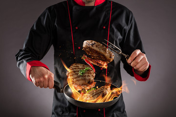 Closeup of chef throwing beef steaks into the air