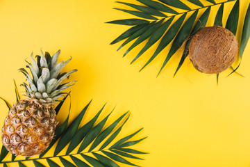 Summer flat lay background. Palm leaves, pineapple and coconut on yellow background.
