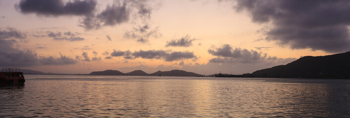Refreshing Panoramic View of romantic sunset sky and seascape in the evening with golden light reflection on water. Summertime, Season, Vacation, Tourist Natural Attraction, Landscape and Destination