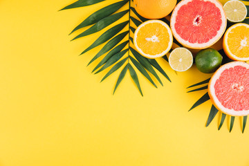 Summer fruits. Tropical palm leaves, lime, grapefruit and orange on yellow background. Flat lay, top view, copy space Fototapete
