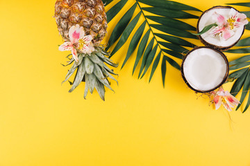 Summer fruits. Tropical palm leaves, pineapple and coconut on yellow background. Flat lay, top view, copy space